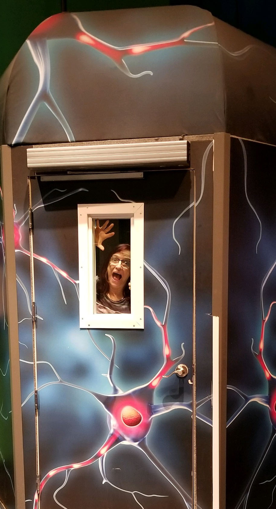 Sharon trapped inside a time machine with frightened face and hands pressed against the window.